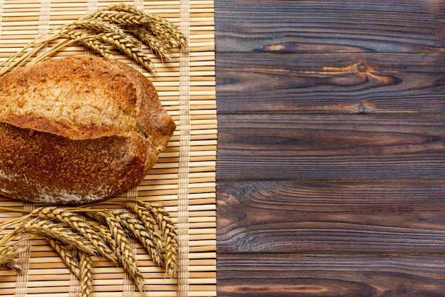 Pane e grano rustici su una vecchia tavola di legno planked dell'annata. sfondo con copyspace