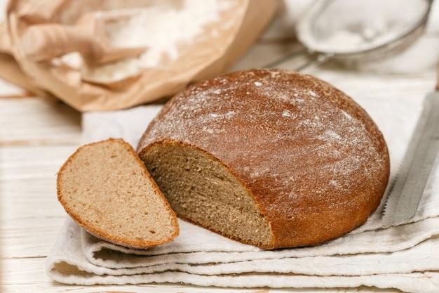 Pane fatto in casa appena sfornato, farina e un coltello su un vecchio tavolo di legno