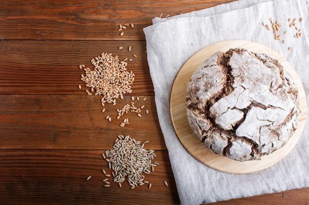 Pane fatto in casa senza lievito con segale integrale e chicchi di grano su fondo rustico in legno.