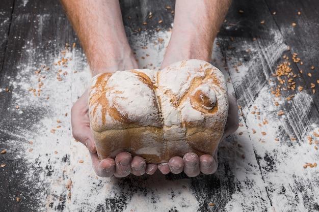 Pane fresco caldo. la cottura e il concetto di cucina. le mani del panettiere tengono con cura la pagnotta sul tavolo in legno rustico, cosparsa di farina. mani sporche macchiate. tonificante morbido