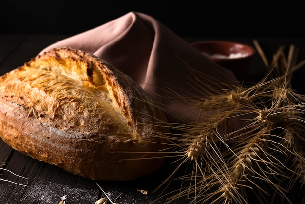 Pane fresco con grano sul tavolo di legno