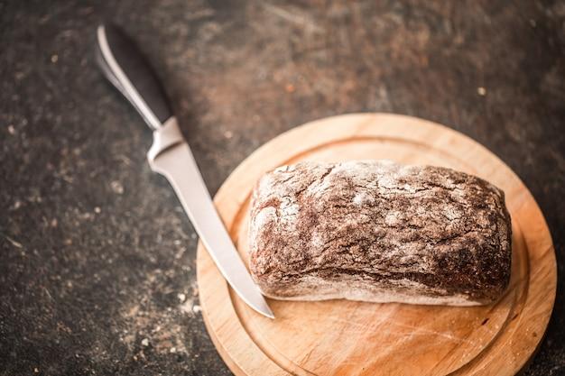 Pane fresco in primo piano delle mani sulla vecchia tavola di legno