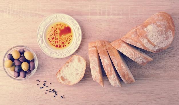 Pane fresco, tagliato a fette con olive e olio d'oliva con aceto balsamico in una ciotola