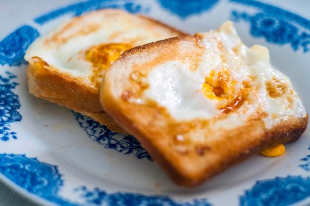Pane gommoso sul piatto, fotografato con luce naturale. pane tostato d'oro francese con burro e uovo. colazione con pane. colazione inglese. colazione sana con uova. colazione gustosa