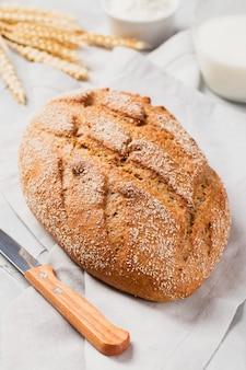 Pane integrale a lievitazione naturale con coltello sul tovagliolo e orecchie di cereali con latte e farina su grigio chiaro chiaro