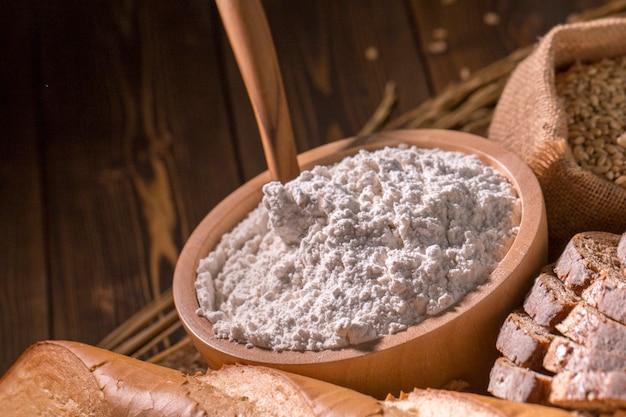Pane integrale, farina soffiata e avena sul tavolo di legno.