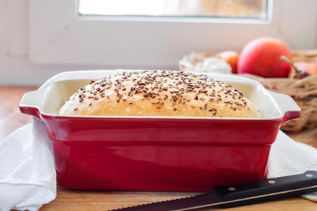 Pane integrale fatto in casa con semi di lino in teglia in ceramica