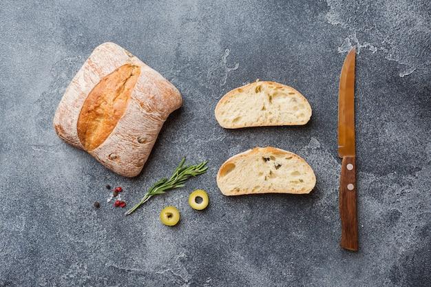 Pane italiano ciabatta con olive e rosmarino su uno sfondo di cemento scuro