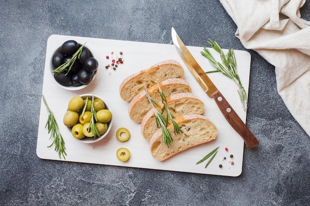 Pane italiano di ciabatta con olive e rosmarino su un tagliere. sfondo scuro di cemento. copia spazio.