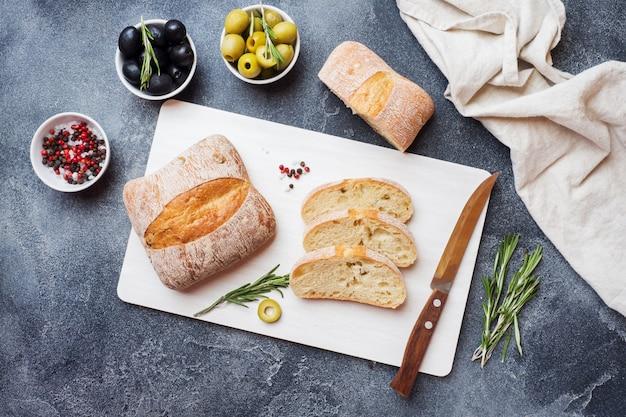 Pane italiano di ciabatta con olive e rosmarino su un tagliere. sfondo scuro di cemento.