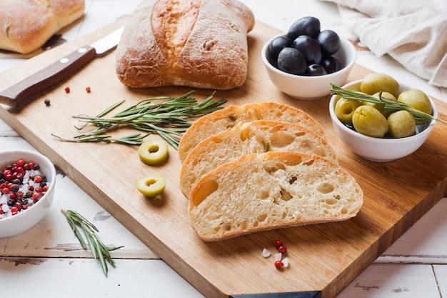 Pane italiano di ciabatta con olive e rosmarino su una tavola di legno