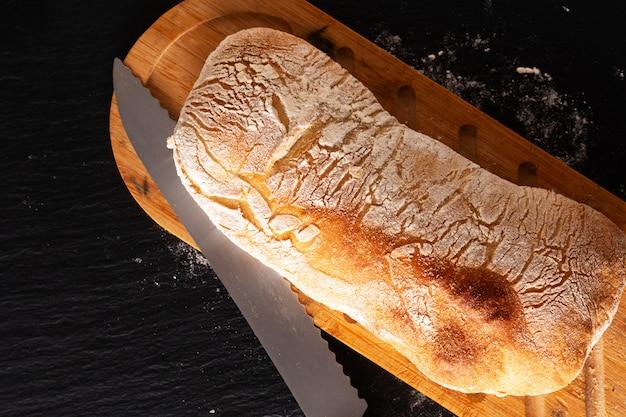 Pane italiano di ciabatta della pasta di lievito di stile italiano artigianale casalingo di concetto dell'alimento sul bordo nero dell'ardesia con lo spazio della copia