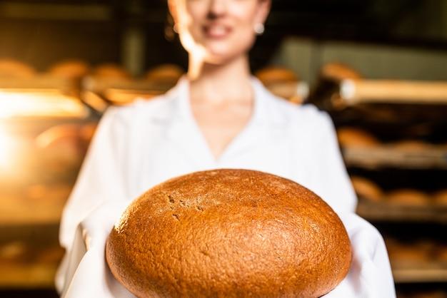 Pane. linea di produzione del pane. pane nella mano della donna.