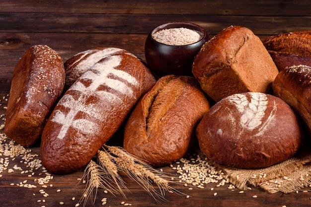 Pane nero al forno fresco su un fondo di legno marrone. pane tradizionale appena sfornato su uno sfondo scuro.