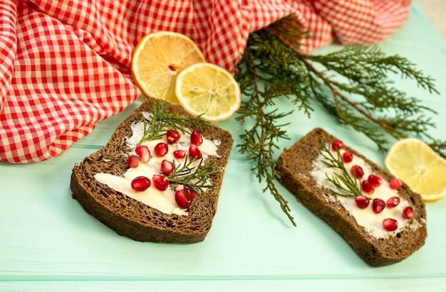 Pane nero con bacche di granate sul fondo in legno turchese. alimento di natale, decorazioni natalizie con limone, ginepro, ramo, bacche rosse