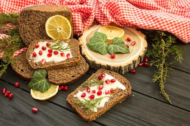 Pane nero con granate bacche su un fondo in legno nero. alimento di natale, decorazioni natalizie con limone, ginepro, ramo, bacche rosse