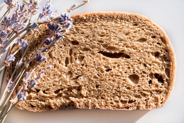 Pane nero tradizionale, close-up di lavanda su uno sfondo bianco. primavera sana colazione estiva