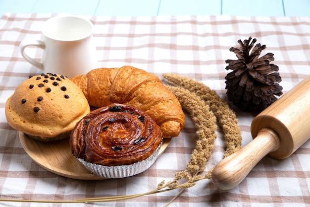 Pane o panino casalingo, croissant e matterello su bianco, concetto dell'alimento di prima colazione e spazio della copia