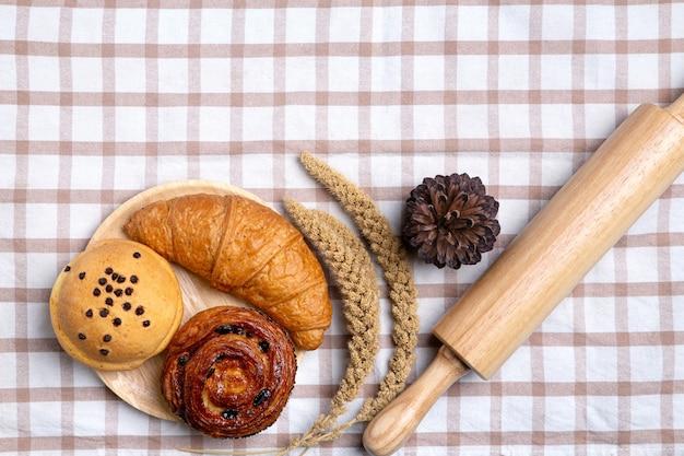 Pane o panino casalingo, croissant e matterello su bianco, vista superiore di concetto dell'alimento di prima colazione e spazio della copia