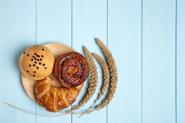 Pane o panino su legno blu, cannella di cornetto, cibo per la colazione