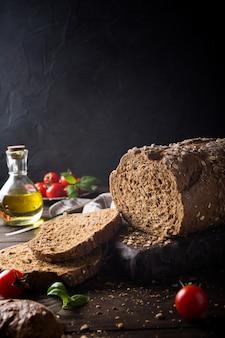 Pane, olio d'oliva, pomodoro e basilico sul tagliere di legno
