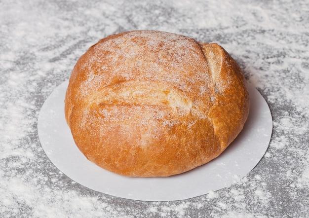 Pane organico senza glutine appena sfornato con farina su fondo grigio