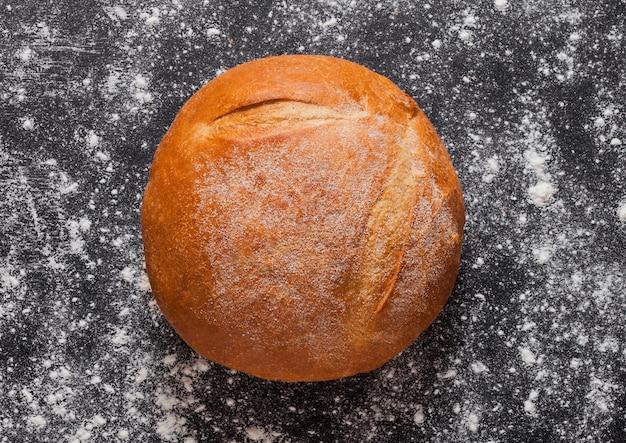 Pane organico senza glutine appena sfornato con farina su fondo nero