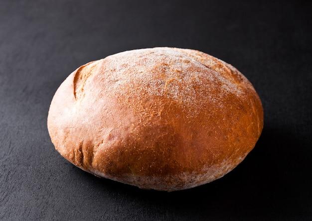 Pane organico senza glutine appena sfornato su fondo nero
