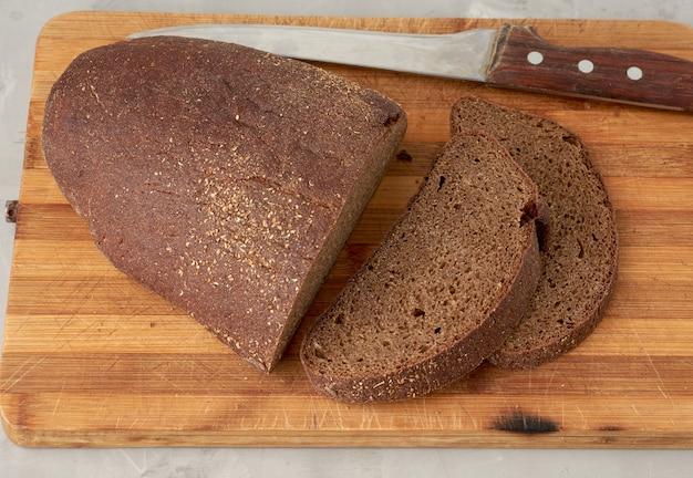 Pane ovale affettato del pane di segale su un bordo di legno