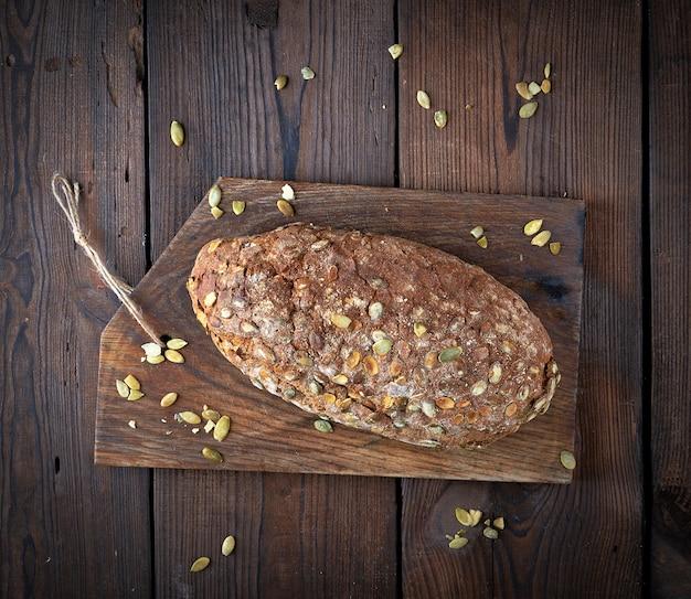 Pane ovale al forno a base di farina di segale con semi di zucca su un tagliere di legno