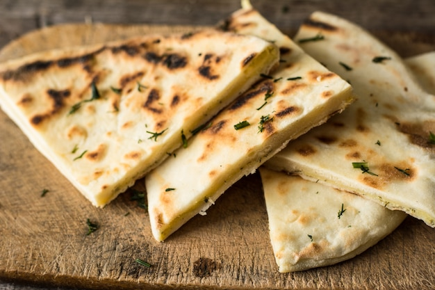 Pane pita su tavola di legno con formaggio feta e pomodori e pepe. cucina georgiana terme