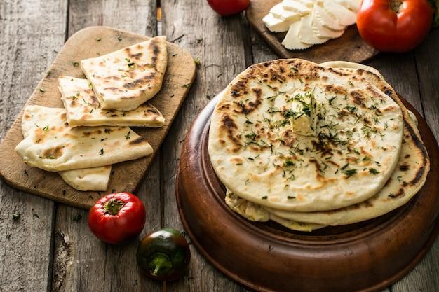 Pane pita su tavola di legno con formaggio feta e pomodori e pepe. natura morta di cibo sol