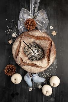 Pane rotondo del grano della segale con i frutti secchi sul nero. decorazioni natalizie, stilizzazione dell'orologio.