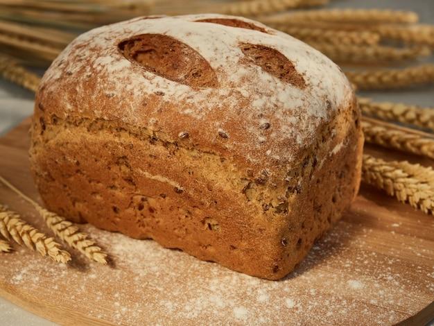 Pane saporito e fragrante, pagnotta intera su una tavola di legno con spighe di grano e chicchi