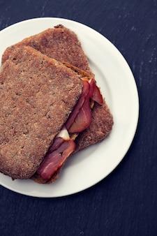 Pane scuro con carne affumicata sul piatto bianco