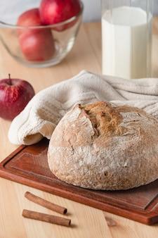 Pane su un tavolo di legno. mele rosse e brocca di latte.