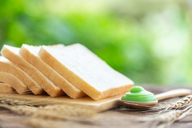 Pane sulla tavola di legno con fondo leggero della sfuocatura verde. concetto di cibo