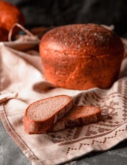 Pane tondo intero con fette sottili su una tovaglia bianca