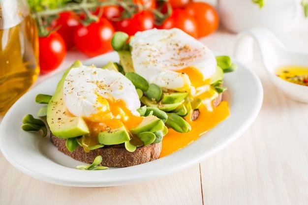 Pane tostato con avocado, pomodorini e uova in camicia su fondo di legno. colazione con cibo vegetariano, concetto di dieta sana.