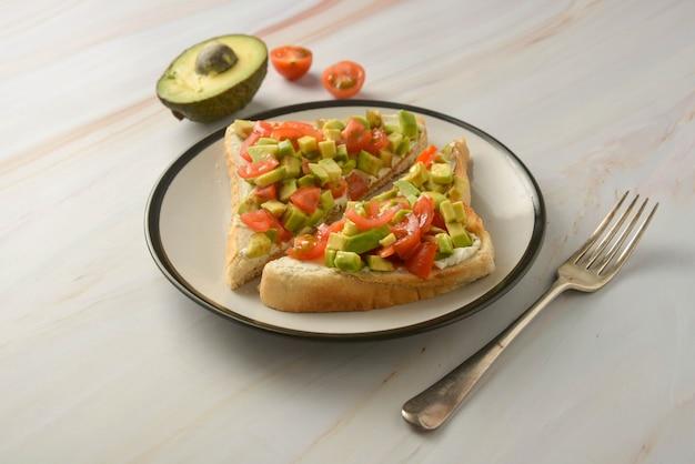 Pane tostato con crema di formaggio, avocado e pomodorini. cibo salutare.