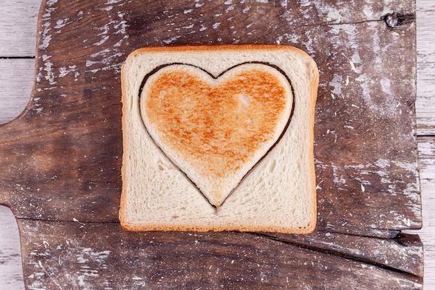 Pane tostato con cuore tagliato sul bordo d'annata, buon san valentino