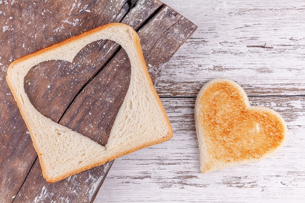Pane tostato con cuore tagliato sul bordo d'annata, concetto felice di san valentino