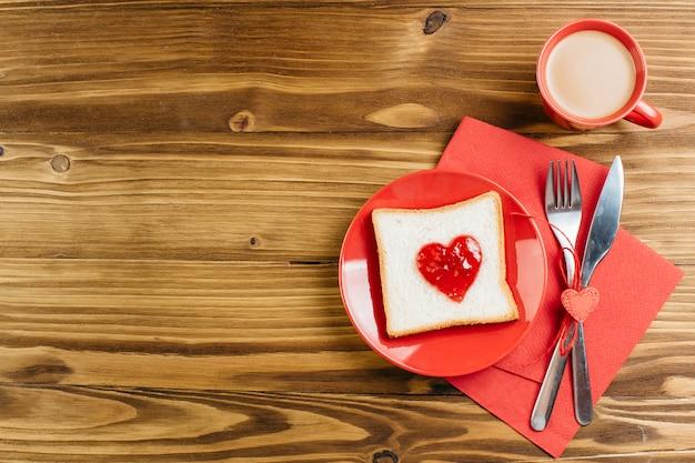 Pane tostato con marmellata a forma di cuore con caffè