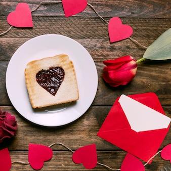 Pane tostato con marmellata sul piatto vicino a cuori di fiori, lettere e ornamenti