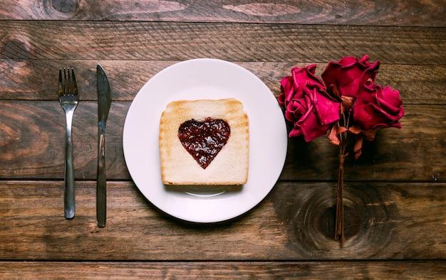 Pane tostato con marmellata sul piatto vicino a fiori e posate