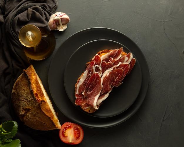 Pane tostato con prosciutto iberico su piatti neri e fondo rustico