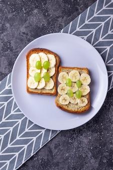 Pane tostato croccante con la banana e l'uva su un pasto sano del fondo grigio