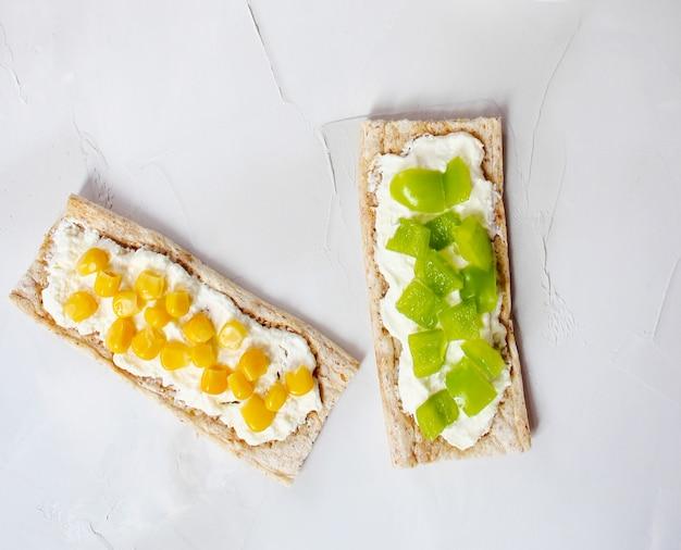 Pane tostato croccante fatto in casa con ricotta e olive verdi, fette di cavolo, pomodori, mais, peperone verde sul tagliere. concetto di cibo sano, vista dall'alto. flat lay