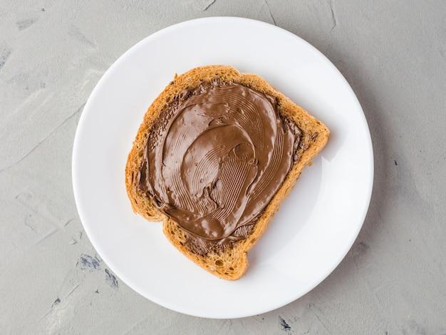 Pane tostato delizioso con pasta di cioccolato su un piatto bianco, primo piano