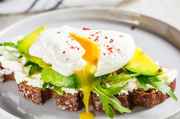 Pane tostato dell'uovo affogato con avocado, crema di formaggio e pane di segale sul piatto grigio. concetto di cibo sano.